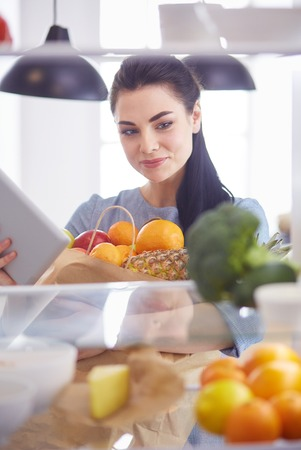 Photo for Smiling woman taking a fresh fruit out of the fridge, healthy food concept - Royalty Free Image