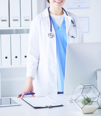 Photo for Young woman doctor at work while pointing at computer in hospital office. - Royalty Free Image