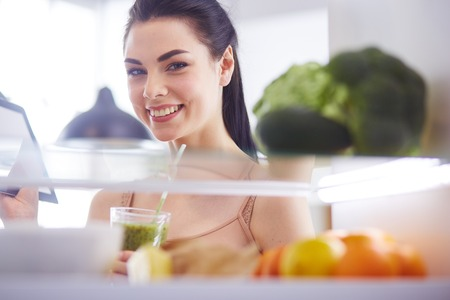 Photo for Smiling woman taking a fresh fruit out of the fridge, healthy food concept. - Royalty Free Image