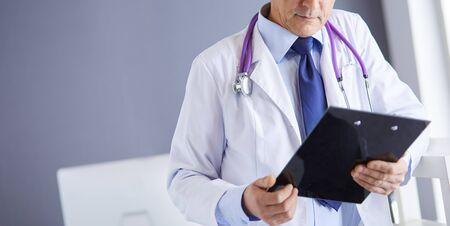 Foto de Male doctor writes notes on the clipboard in the hospital - Imagen libre de derechos
