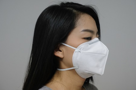 Photo pour Woman wearing face mask of N95 because of air pollution in the city have particulate matters or PM 2.5. - image libre de droit