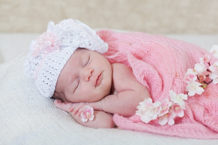 Foto de  newborn girl sleeps with spring flowers under a knitted pink cape - Imagen libre de derechos