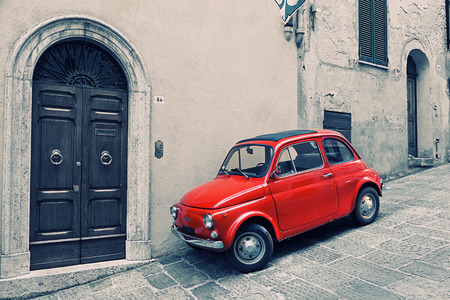 Foto de ITALY, MONTEPULCHANO - MAY 16, 2014: Old red Fiat 500 R to stand near a wall. Fiat Nuova 500 (ital. cinquecento) — the car made by the Fiat company with 1957 on 1975 - Imagen libre de derechos