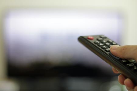 Foto de hand with remote control and TV set in the background - Imagen libre de derechos