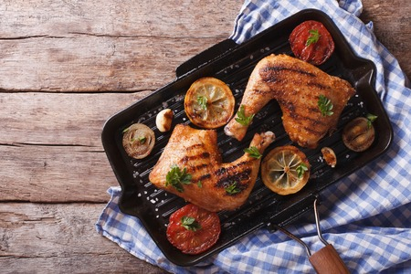 Grilled chicken leg and vegetables on the grill pan. horizontal view from above, rustic style