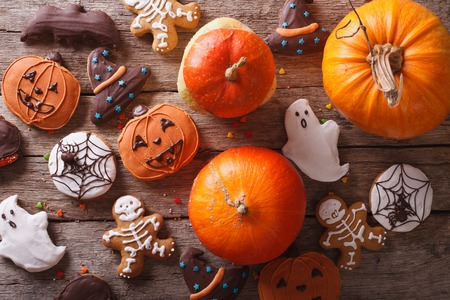 Beautiful gingerbread for Halloween and fresh pumpkin on the table. horizontal view from above