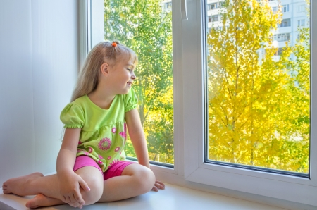Photo for Cheerful girl sitting by the window - Royalty Free Image