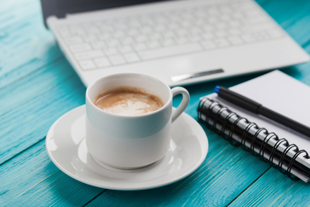 Foto de Office items with cup of coffee, notepad, pen and laptop on a blue turquoise table - Imagen libre de derechos