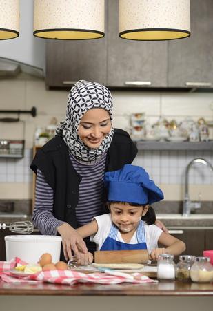 Photo for Moslem woman wearing hijab, teaching her daughter make halal food - Royalty Free Image