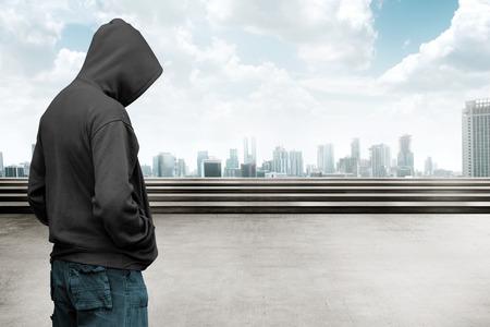 Photo pour Faceless man in hood with cityscape background - image libre de droit