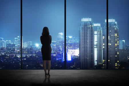 Photo pour Woman standing in his office looking at the city at night. Business success concept - image libre de droit