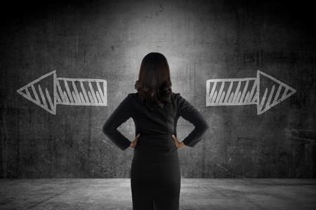 Foto de Business woman has to choose between two way. Business option conceptual - Imagen libre de derechos