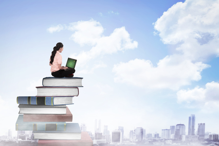 Foto de Business person working with laptop on  the top of books. Career and education concept - Imagen libre de derechos