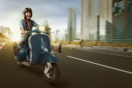 Photo pour Asian woman riding scooter and wearing helmet on the street - image libre de droit