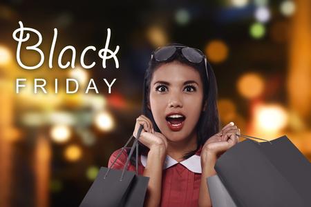 Foto de Happy asian woman with shopping bags on Black Friday celebration - Imagen libre de derechos