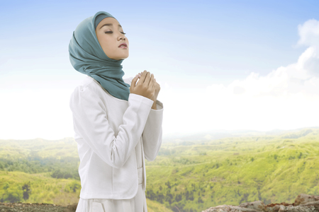 Photo pour Pretty asian muslim woman wearing hijab raising hand and praying with landscape view background - image libre de droit