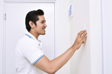 Photo pour Handsome asian man turning off the light with wall switch in the home - image libre de droit