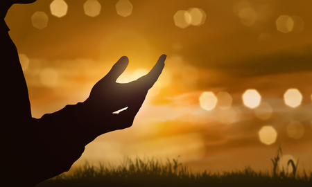 Foto de Silhouette of human hand with open palm praying to god at sunset background - Imagen libre de derechos