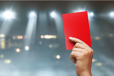 Photo pour Referee hands showing red card on football match - image libre de droit