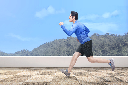Photo pour Handsome asian man running outdoors with green hills background - image libre de droit
