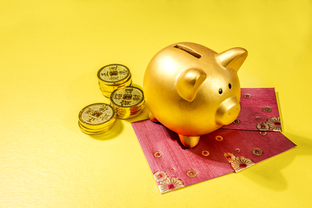 Photo pour Piggy bank with golden coins and red envelopes over yellow background. Chinese New Year. Year of the earth pig - image libre de droit