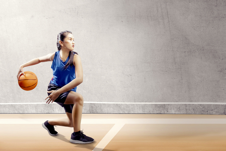 Foto de Attractive asian girl in blue sport uniform on basketball pivot moves on the basketball court with wooden floor and concrete wall background - Imagen libre de derechos