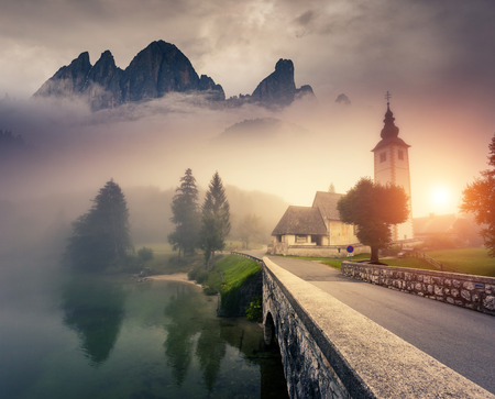 Photo pour Majestic colorful foggy morning scene in the Triglav national park, located in the Bohinj Valley of the Julian Alps. Dramatic view of the church St. John the Baptist. Slovenia, Europe. Beauty world.. - image libre de droit