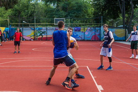 Photo pour ODESSA, UKRAINE - JULY 28, 2018: Adolescents play basketball during 3x3 streetball championship. Young people play street basketball on an open city sports ground. Streetball - street cultures - image libre de droit