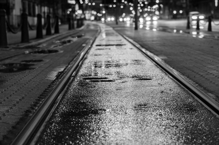 Photo pour Night view on wet tram rails after rain. Blurred traffic lights on background, black and white tone - image libre de droit