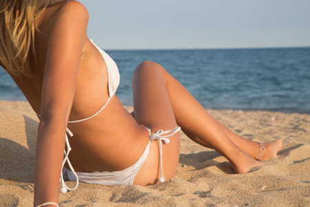 Beautiful girl lying on the beach with the sea in background, Bodyparts