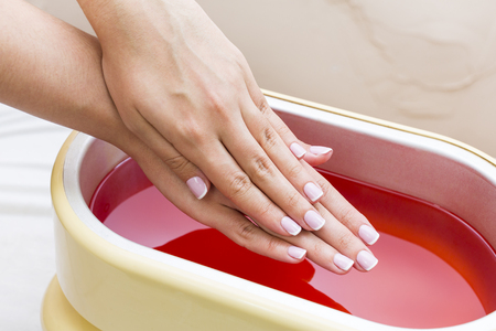 Photo for Process paraffin treatment of female hands in beauty salon - Royalty Free Image