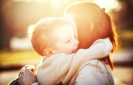 Photo for Mother hugging her child druing walk in the park - Royalty Free Image