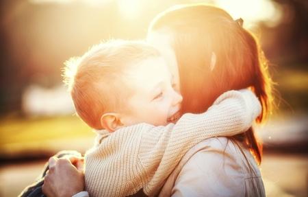 Foto de Mother hugging her child druing walk in the park - Imagen libre de derechos