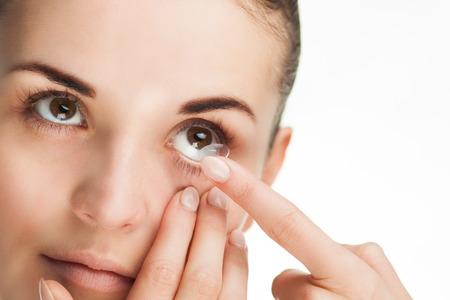 Foto de Woman putting contact lens in her eye concept of healthcare - Imagen libre de derechos