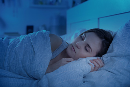 Photo pour Woman peacefully sleeping in bed at night - image libre de droit