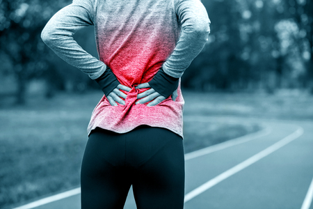 Photo pour Athletic woman on running track touching hurt back with painful injury during workout - image libre de droit