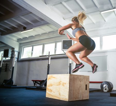 Photo for Fitness woman jumping on box training at the gym, crossfit exercise - Royalty Free Image