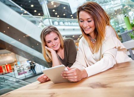 Two woman friends using digital tablet watching media content in cafe at shopping mall