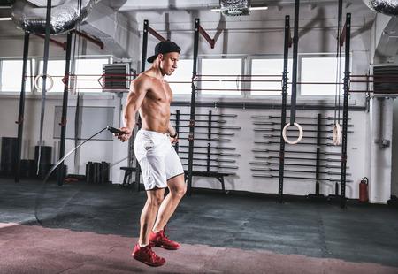 Foto de Muscular man skipping exercise with jumping rope at gym - Imagen libre de derechos