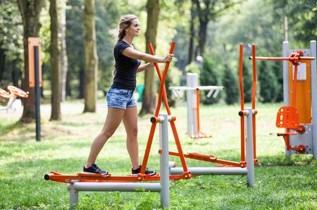 Photo pour Woman exercising at outdoors gym playground equipment - image libre de droit