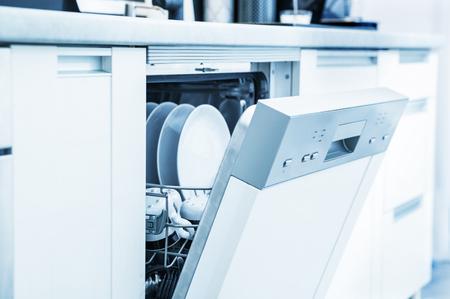 Foto de Open dishwasher with clean dishes in the white kitchen - Imagen libre de derechos
