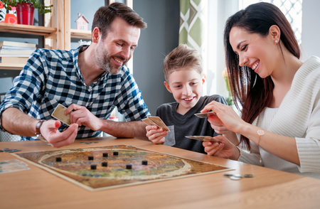 Foto de Happy family playing board game at home, happiness concept - Imagen libre de derechos