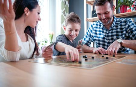 Foto de Happy family playing board game at home, happiness concept - Imagen libre de derechos