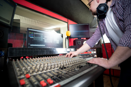 Photo for Sound producer working at recording studio using soundboard and monitors - Royalty Free Image