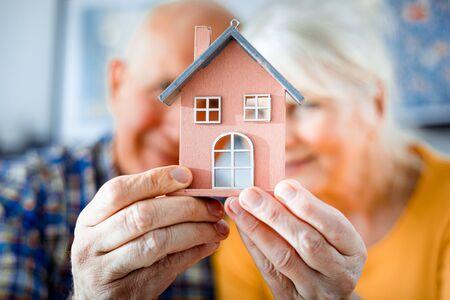 Photo pour New house concept, happy senior couple holding small home model - image libre de droit