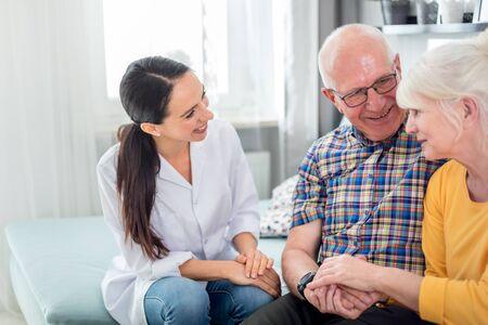 Foto de Smiling nurse talking with senior couple during home visit - Imagen libre de derechos