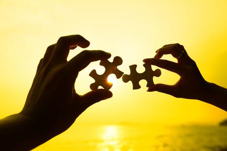 Foto de Two hands trying to connect puzzle pieces with sunset background - Imagen libre de derechos