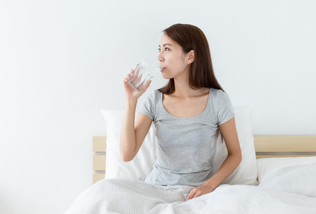 Photo pour Woman drink a glass of water at morning - image libre de droit