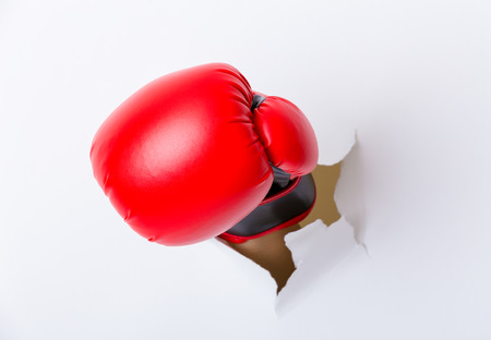 Foto de Hand break through paper with boxing gloves - Imagen libre de derechos