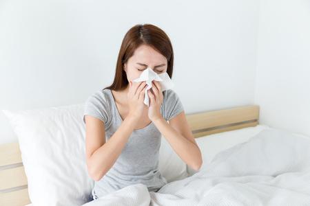 Foto de Asian woman feeling unwell and sneeze on bed - Imagen libre de derechos